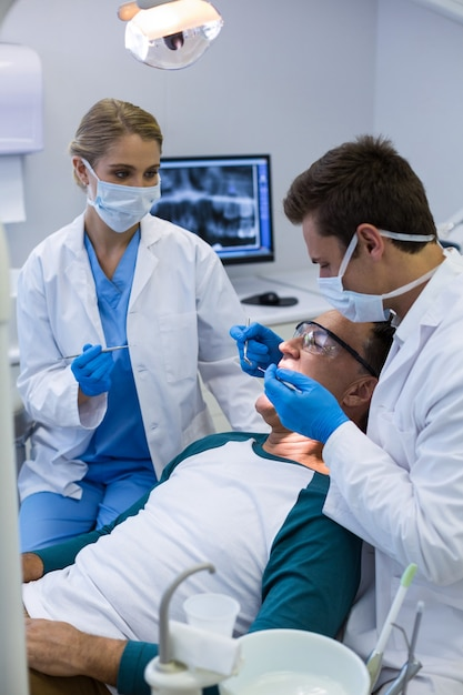 Tandartsen die een mannelijke patiënt met hulpmiddelen onderzoeken Premium Foto
