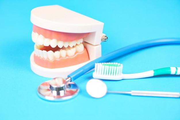 Tandheelkundige zorg tandarts tools met kunstgebit tandheelkunde instrumenten en tandhygiëne en apparatuur controle met tanden model en mond spiegel mondgezondheid Premium Foto