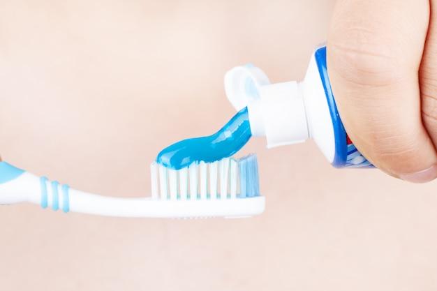 Tandpasta wordt toegepast op de tandenborstel, concept: tandenpoetsen Premium Foto