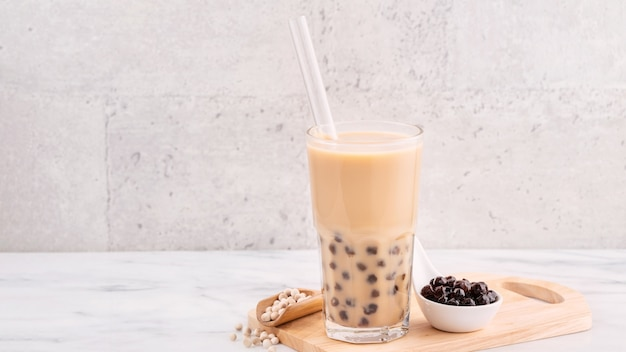 Tapioca pearl ball bubble milk tea, populaire taiwanese drank, in drinkglas met rietje op marmeren witte tafel en houten dienblad Premium Foto