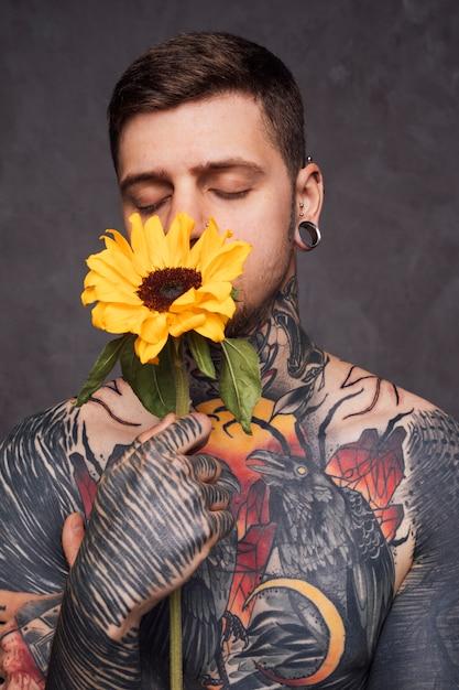 Tatoeëren jonge man met holdingszonnebloem voor zijn mond tegen grijze achtergrond Gratis Foto