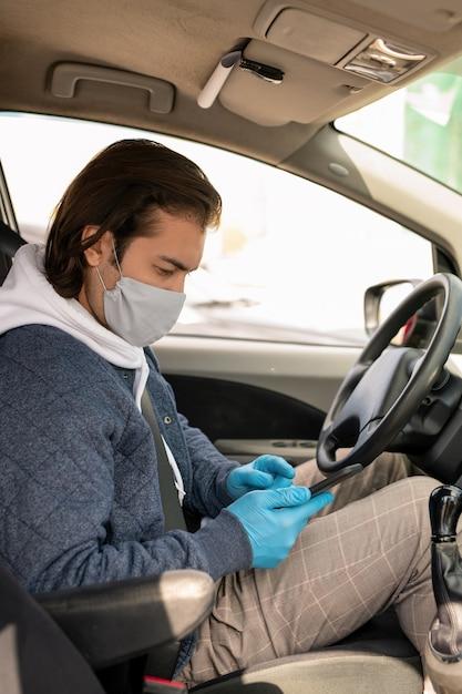 Taxichauffeur van middelbare leeftijd in doekmasker en handschoenen die met mobiele app werken tijdens het uitvoeren van ritten Premium Foto