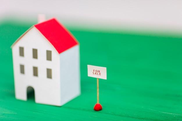 Te koop tag in de buurt van het onscherpe huis model op groene bureau Gratis Foto