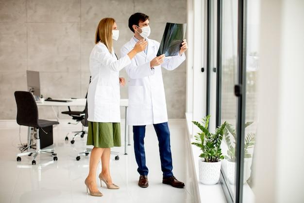 Team van artsen met beschermende gezichtsmaskers xray in het kantoor te onderzoeken Premium Foto