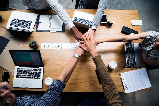 Team van bedrijfsmensen die handen stapelen Gratis Foto