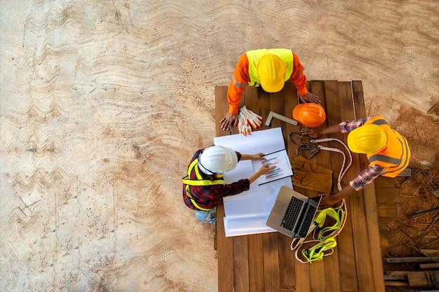 Team van ingenieur en architecten werken, ontmoeten, bespreken, ontwerpen, plannen, meten lay-out van het bouwen van blauwdrukken op de bouwplaats, bovenaanzicht, bouwconcept. Premium Foto