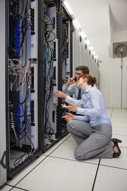 Team van technici geknield en kijkend naar servers Premium Foto