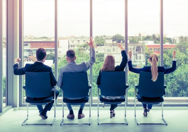 Team van werknemer viert succes aan de vensters Premium Foto