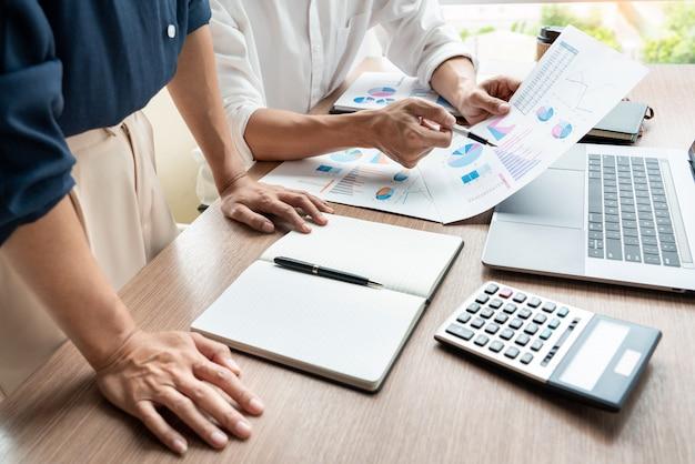 Teamwerkconcept, directeuren die het documentwerk bespreken op vergadering in moderne bureauhal. Premium Foto