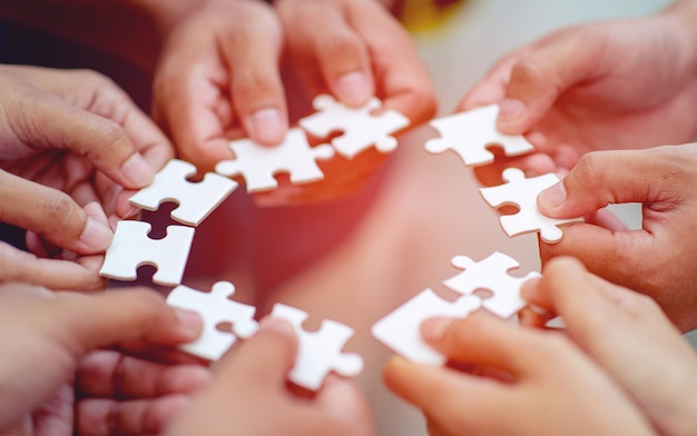 Teamwork, hands and jig saw unite with power is een goed team van succesvolle mensen teamwork concept Premium Foto