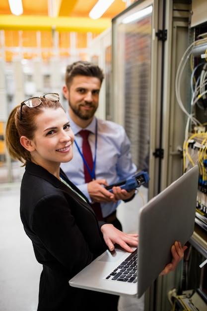 Technici die laptop gebruiken tijdens het analyseren van de server Premium Foto