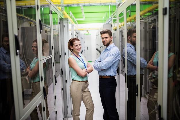 Technici die zich met wapens bevinden die in een serverruimte worden gekruist Premium Foto