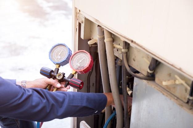 Technicus controleert airconditioner meetapparatuur voor het vullen van airconditioners. Premium Foto