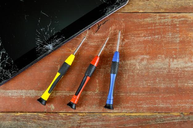 Technicus die binnenkant van tablet herstelt door schroevedraaier in de mobiele telefoon elektronische het herstellen technologie. Premium Foto