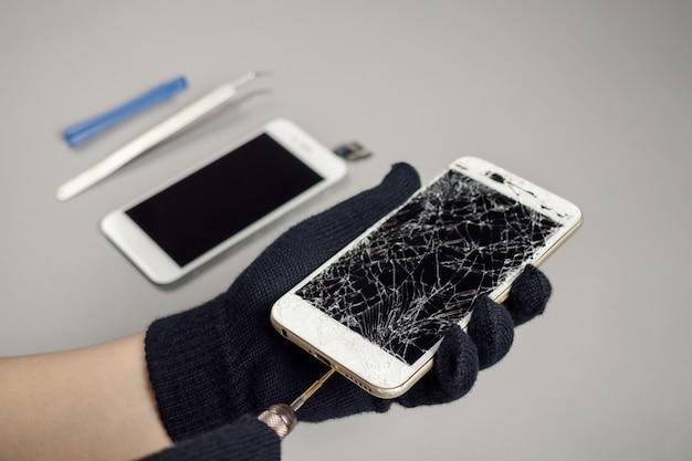 Technicus die gebroken smartphone op bureau herstelt Premium Foto