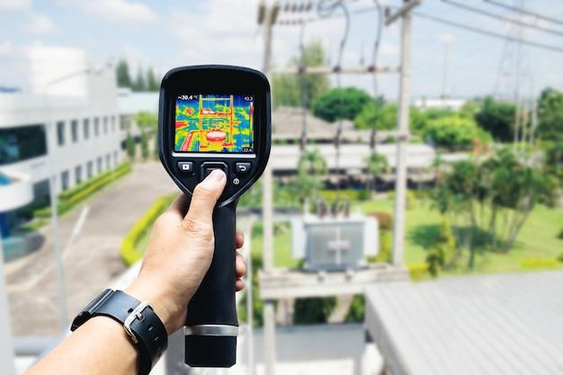 Technicus gebruik warmtebeeldcamera om de temperatuur in de fabriek te controleren Premium Foto