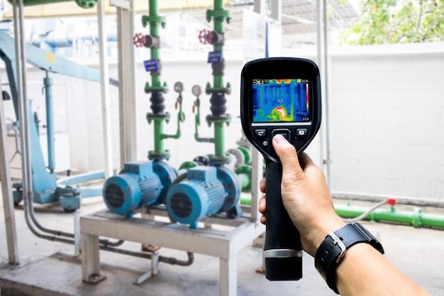 Technicus gebruikt warmtebeeldcamera om de temperatuur in de fabriek te controleren Premium Foto