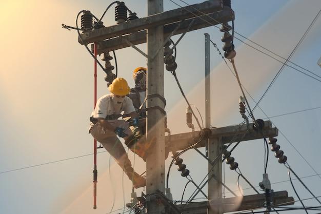 Technicus werkt op hoogspanningselektriciteitspool en reflecteert licht Premium Foto