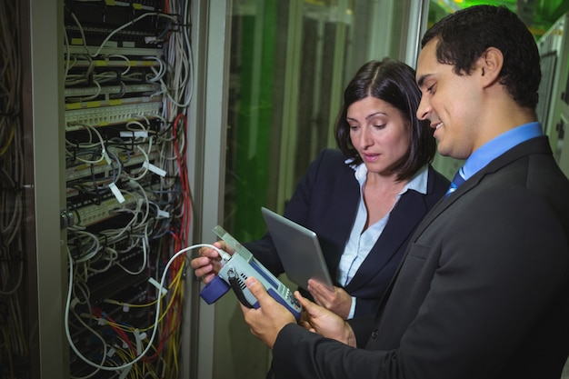 Technicus werkt op personal computer tijdens het analyseren van server technici die digitale kabelanalyses gebruiken Premium Foto