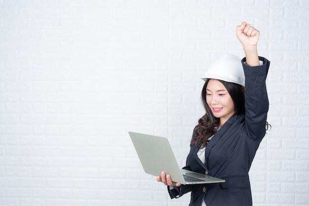 Techniekvrouw die een afzonderlijk notitieboekje, witte bakstenen muur houden maakte gebaren met gebarentaal. Gratis Foto