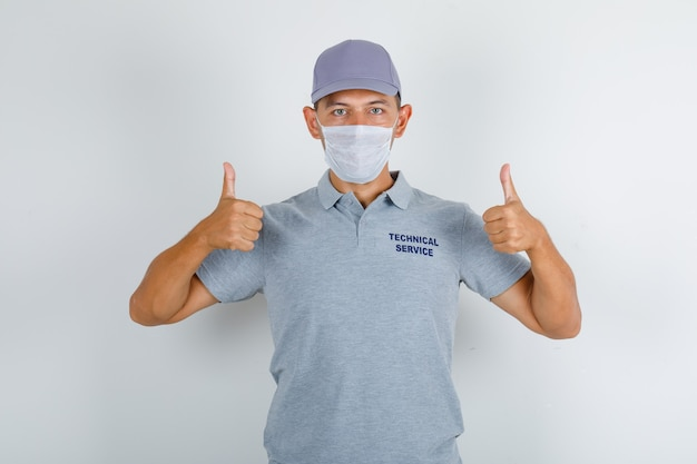Technische dienst man duimen opdagen in grijs t-shirt met pet en medisch masker en voorzichtig kijken Gratis Foto