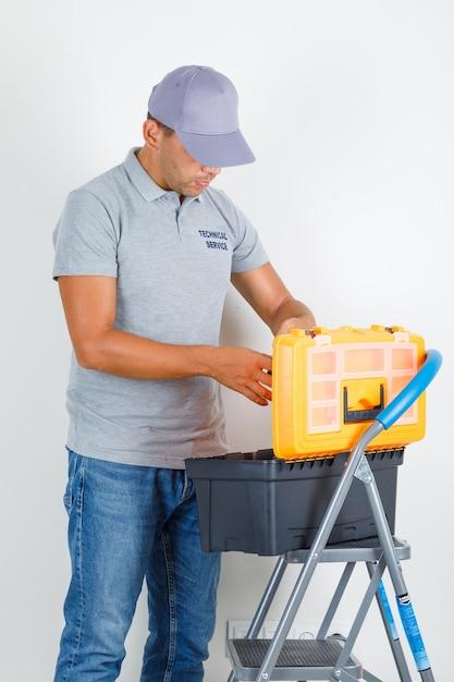 Technische dienst man op zoek naar toolbox in grijs t-shirt met pet en op zoek naar druk Gratis Foto