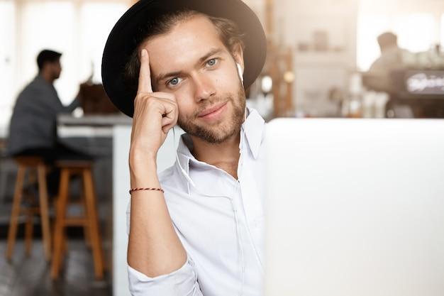 Technologie en communicatieconcept. stijlvolle jongeman met baard met zwarte hoed luisteren naar muziek op witte koptelefoon zit generieke laptopcomputer, leunend op zijn elleboog en glimlachen Gratis Foto