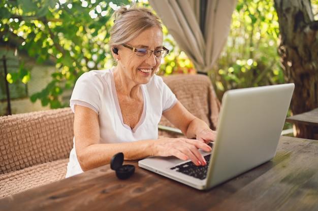 Technologie, ouderen mensen concept - bejaarde gelukkig senior vrouw met behulp van draadloze hoofdtelefoons online werken met laptop buiten in de tuin. werken op afstand, onderwijs op afstand. Premium Foto