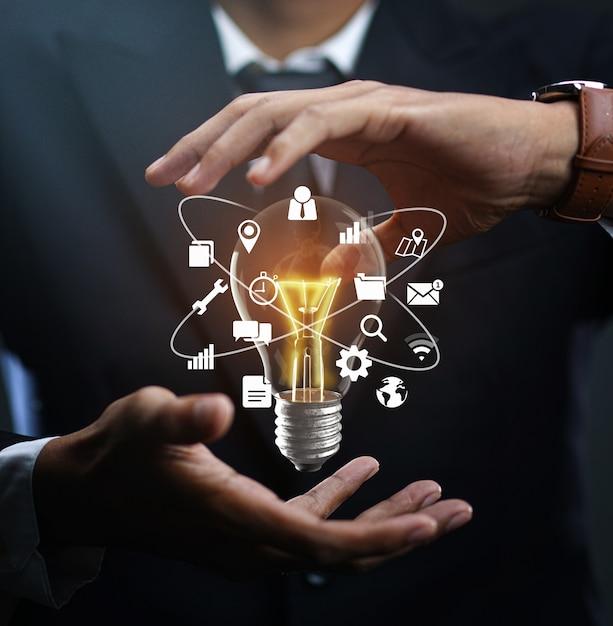Technologie pictogrammen gloeiende lamp drijvend op zakenmanhand. Premium Foto