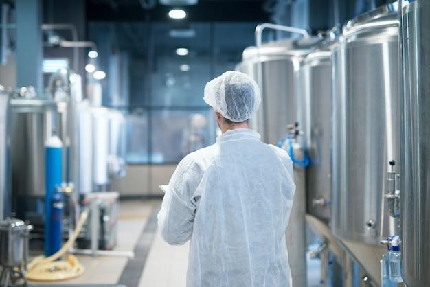 Technoloog die in wit beschermend pak door de productielijn van de voedselfabriek loopt die kwaliteit controleert Gratis Foto
