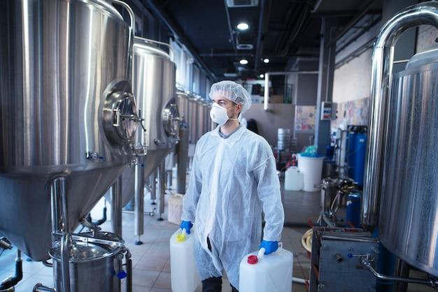 Technoloog fabrieksarbeider met plastic jerrycans die op het punt staan chemicaliën in de voedselverwerkingsmachine te veranderen Gratis Foto