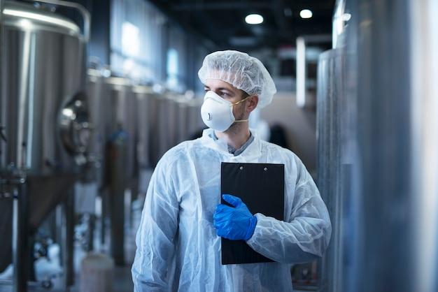 Technoloog in beschermend wit pak met haarnetje en masker staande in voedselfabriek Gratis Foto