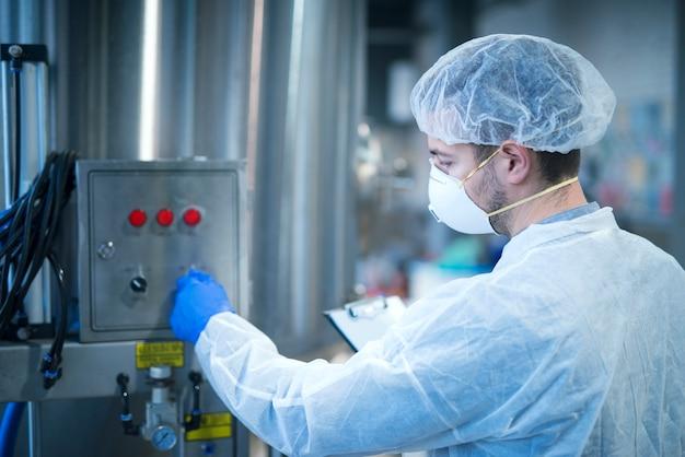 Technoloog in beschermende uniforme operationele industriële machine in de productielijn van de fabriek Gratis Foto