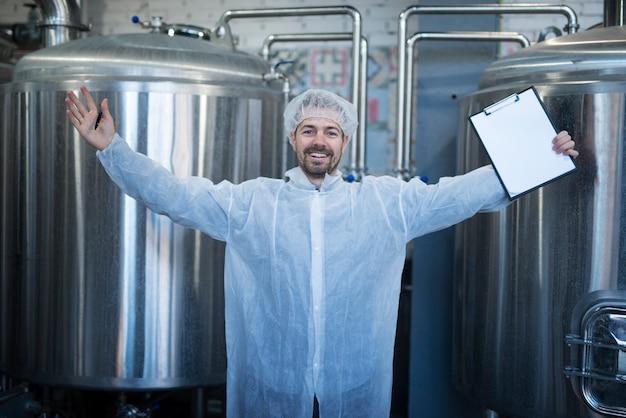 Technoloog in wit beschermend pak met opgeheven handen die succes en goede resultaten in voedselfabriek vieren Gratis Foto