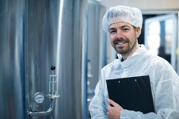 Technoloog in wit beschermend uniform en haarnetje permanent door chroomreservoirs met manometer in voedselverwerkende fabriek Gratis Foto