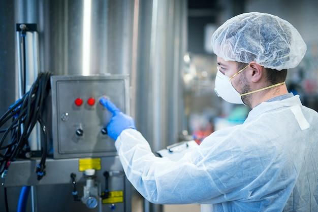 Technoloog in wit beschermend uniform met haarnetje en masker op industriële machine voor voedselverwerking Gratis Foto
