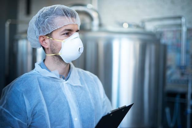 Technoloog werkzaam in de voedselverwerkende fabriek voor medische productie die kwaliteit en distributie controleert Gratis Foto