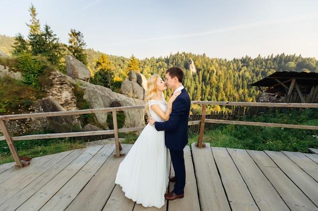 Teder kussend paar tegen rotsen en ver de herfstbos Premium Foto