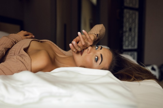 Tedere jonge blonde liggend op het bed in de hotelkamer, ze is eenzaam en wacht op de man van haar leven. slanke vingers bij de lippen, blauwe ogen die door het raam kijken. naakt stijlvolle make-up en haar. Gratis Foto