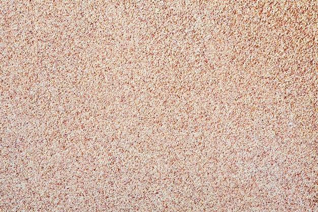 Tegen de achtergrond van verspreid zand klein grind, een stenen kruimel. het patroon van een oppervlak van een muur, lichte kleur Premium Foto