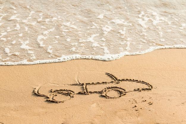 Teken auto op strandzand. conceptueel ontwerp. beeld van auto op het zand autotekening in het zand dichtbij overzees. ruimte voor tekst Premium Foto