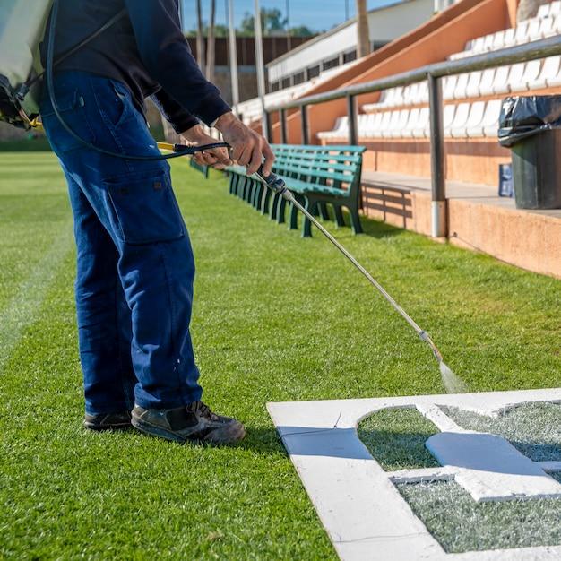 Teken letters op het gras in het wit over een sjabloon. de naam van het voetbalveld op het gras Premium Foto