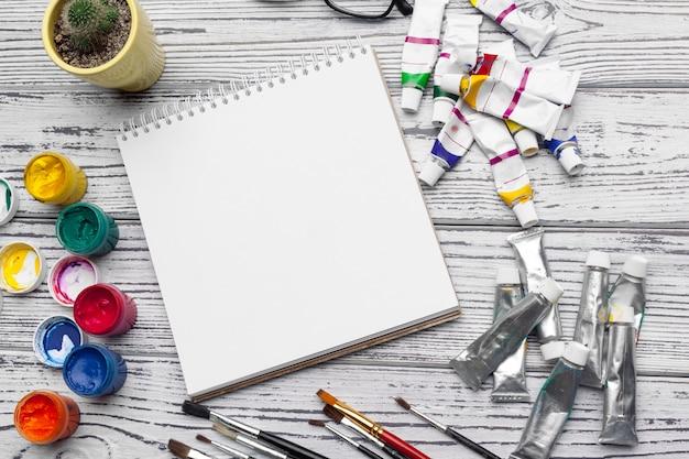 Tekengereedschappen, stationaire benodigdheden, werkplek van kunstenaar. waterverfverven en lege blocnote op houten bureau Premium Foto