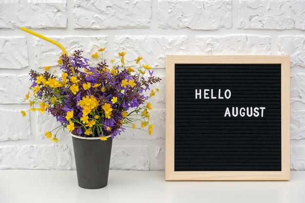 Tekst hallo augustus op zwart letterbord en boeket van gekleurde bloemen in zwart papieren koffiekopje Premium Foto