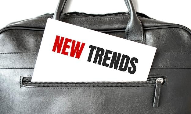 Tekst nieuwe trends schrijven op wit vel papier in de zwarte zakelijke tas. Premium Foto