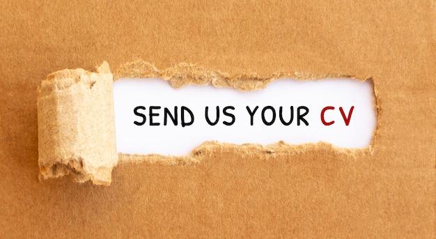 Tekst stuur ons uw cv achter gescheurd bruin papier. Premium Foto