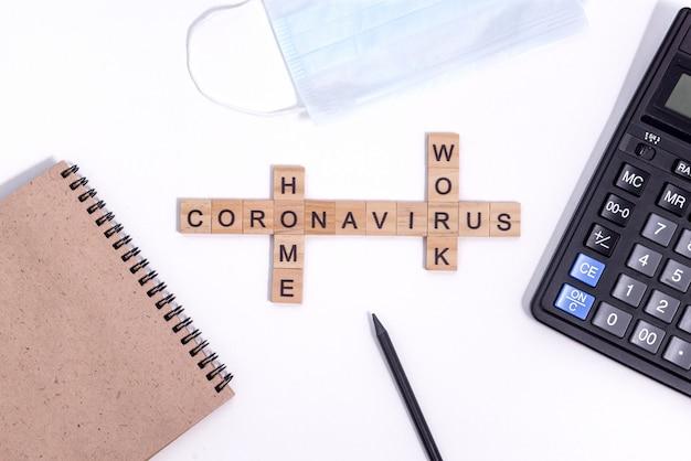 Tekst uit houten brieven coronavirus werken vanuit huis. kantoorartikelen, een rekenmachine, papier kladblok voor notities, een potlood en een beschermend medisch masker op het bureaublad. Premium Foto