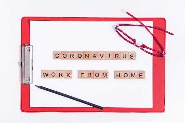 Tekst uit houten brieven coronavirus werken vanuit huis. kantoorartikelen, een rode tablet, potlood en een bril op het bureaublad. werken tijdens een viruspandemie. Premium Foto