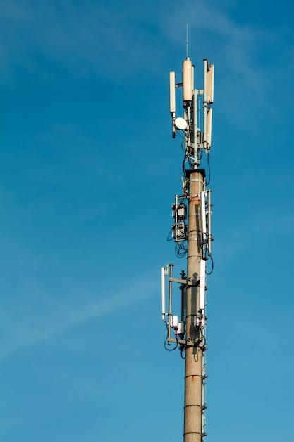 Telecommunicatiemast tegen blauwe hemel en grote witte wolk Premium Foto