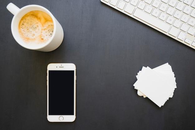Telefoon, kaarten, koffie en toetsenbord Gratis Foto
